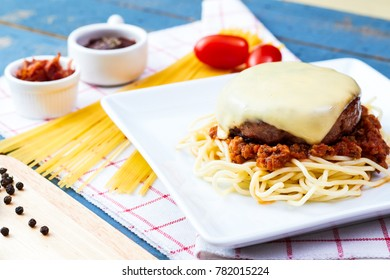 Cheese burger and spaghetti meat sauce homemade on the wooden table.
