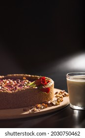 Cheese cake with peanuts on wooden plate and with fllowers on it and glass of milk, on black background.
