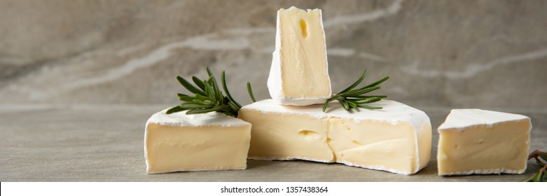 Cheese camembert or brie with rosemary on cutting board on marble stone background. Copy space.  Studio photo.