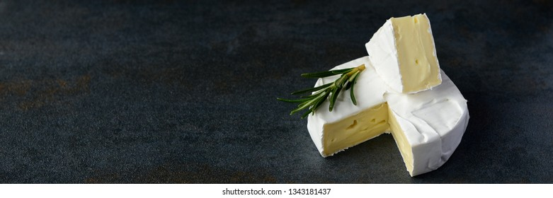 Cheese camembert or brie with rosemary and pepper on dark stone background. Copy space.  BannerStudio photo.