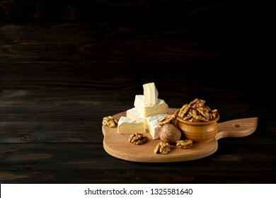 Cheese camembert or brie with walnut kernels on cutting board on dark wooden background. Copy space.  Studio photo.