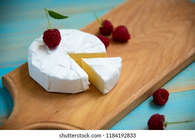 cheese camembert with raspberries and grapes on a blue background