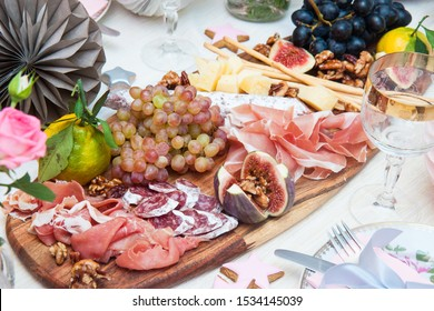 Cheese and charcuterie serving board with parmesan, prosciutto, salami, grapes, figs, bread, pecan nuts, ham and bread sticks. Roses, pumpkin and paper balloons are on the background.