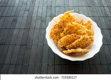 Cheese Chips Snack in a round white bowl on a black wooden background. Grain Free Dippable Crispy Cheddar Cheese Chips, Keto & Low Carb. Crunchy chip from cheddar, parmesan, asiago, herbs, spices