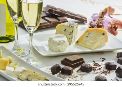 Cheese, chocolates, wine, and orchid on white