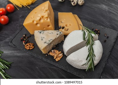 Cheese collection with different food ingredients on the black table, top view