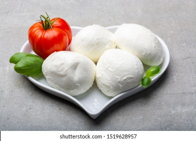 Cheese collection, Italian soft white cheese mozzarella in balls with tomato and basil, love mozzarellaa concept with heart plate
