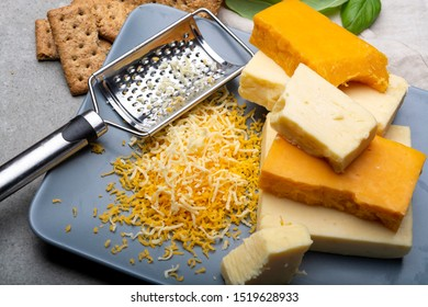 Cheese collection, matured and orange original British cheddar cheese in blocks and grated served on grey plate close up
