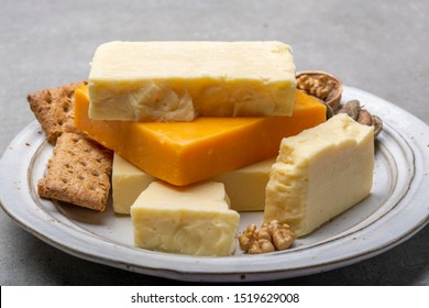 Cheese collection, matured and orange original British cheddar cheese in blocks served with crackers close up