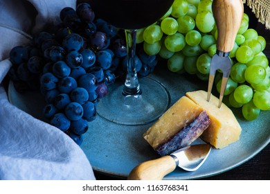Cheese concept with famous georgian suluguni cheese in saperavi wine with fruits and spices on rustic background