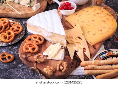 Cheese and cracker appetizer selection.  bread sticks, slices, olives, sun-dried tomatoes, grapes and nuts on rustic wooden board over dark backdrop, top view