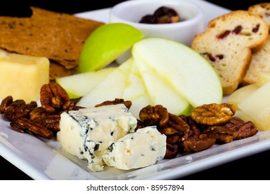 Cheese, crackers, fruit and nuts on a platter.