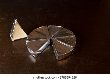 Cheese in creamy triangular shapes, wrapped in aluminum foil