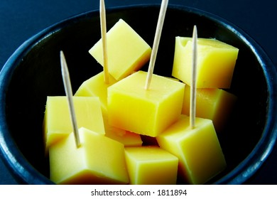 Cheese cubes with toothpicks - black background