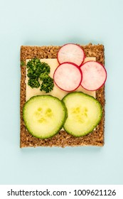 Cheese and Cucumber Open Face Rye Bread Sandwich With Radishes Against a Light Blue Background