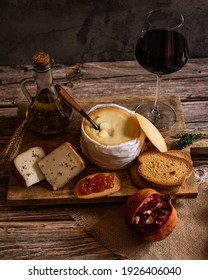 cheese and a cup of wine in a wooden table