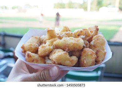 Cheese curds on a paper plate at a baseball game.
