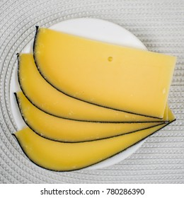 Cheese cut into slices on a white plate.