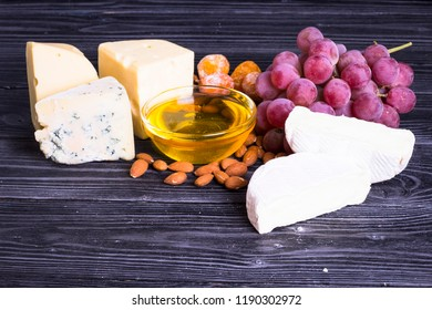 Cheese cuts with figs, nuts, honey, grapes on a dark rustic wooden boards background. Top view