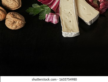 Cheese delikatessen closeup on black stone desk surface. Camembert or brie circle in brown kraft paper decorated with basil and pieces of cherry tomatoes, top view image with copy space.