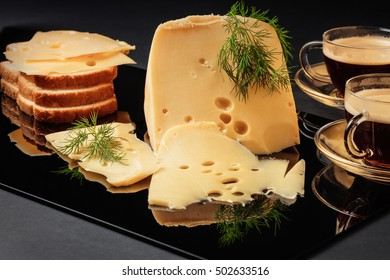 Cheese with fennel, white loaf and two cups of coffee on a black background