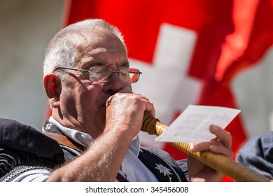 Cheese festival, Gruyere, Switzerland - May 4, 2014. Swiss musician plays the alphorn, typical instrument on the main street of the Gruyere village on May 4, 2014. Swiss flag on background.