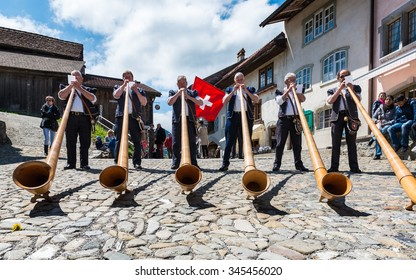 Cheese festival, Gruyere, Switzerland - May 4, 2014. Swiss musicians play the alphorn, typical instrument on the main street of the Gruyere village on May 4, 2014
