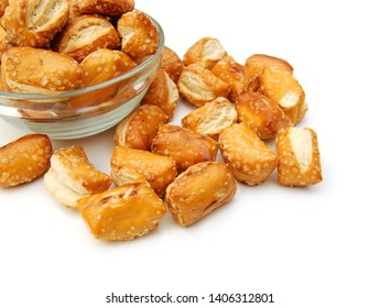 Cheese filled, bite-sized pretzel sticks in glass bowl on white background