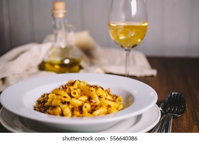 Cheese flavored rigatoni pasta in a white plate on a wooden table with kitchen appliances, glass of dry white wine and glass jug with olive oil on the old gray kitchen towel in the background