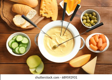 Cheese fondue in pot and different products on wooden table