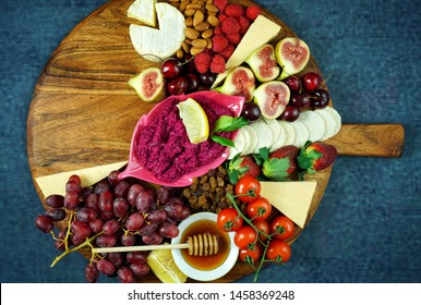 Cheese and fruit charcuterie dessert grazing platter on wooden board overhead with copy space.