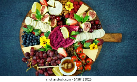 Cheese and fruit charcuterie dessert grazing platter on wooden board overhead.