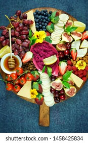 Cheese and fruit charcuterie dessert grazing platter on wooden board overhead.