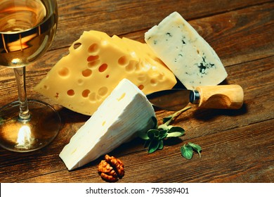 Cheese and a glass of white wine on an old wooden table with nuts and a knife for cheese.