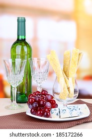 Cheese, grape and bread sticks on plate on wooden table, on bright background