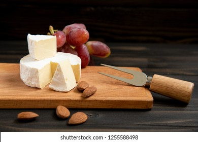 Cheese and grapes, almond. Slices of cheese camembert with grapes and nuts, melange on a dark background. Camembert cheese. Top view