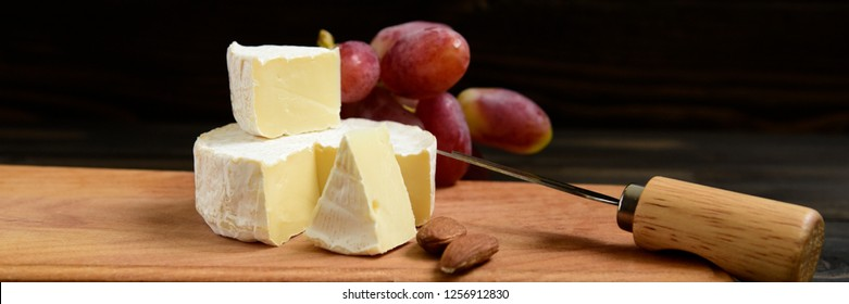 Cheese and grapes, almond. Slices of cheese camembert with grapes and nuts, melange on a dark background. Camembert cheese.