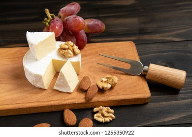 Cheese and grapes, almond, walnut. Slices of cheese camembert with grapes and nuts, melange on a dark background. Camembert cheese.