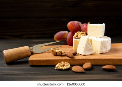 Cheese and grapes, almond, walnut. Slices of cheese camembert with grapes and nuts, melange on a dark background. Camembert cheese