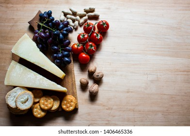 Cheese with grapes and cherry tomatoes, cracker, nuts, fruits and nuts. View from above. Cheese on a visible background. Copy space