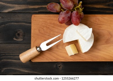 Cheese and grapes. Slices of cheese camembert with grapes and nuts, melange on a dark background. Camembert cheese. Top view