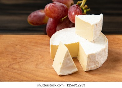Cheese and grapes. Slices of cheese camembert with grapes and nuts, melange on a dark background. Camembert cheese