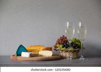 Cheese and grapes in wicker basket with white wine in glasses standing against grey wall