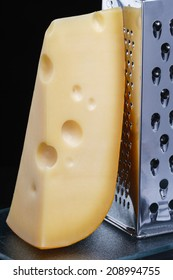 cheese and grater on a  reflective surface