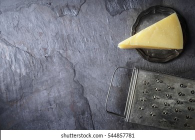 Cheese and grater on the stone background top view