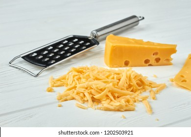 Cheese and grater on white background. Grated cheese on wooden table. Delicious Dutch cheese.