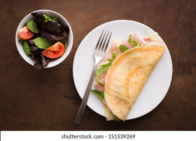 Cheese and ham crepe with salad overview