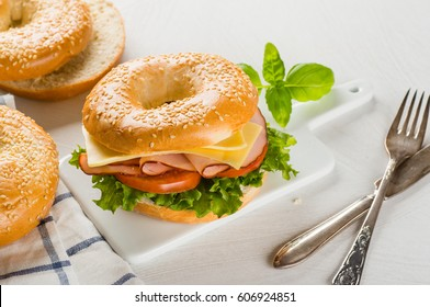 cheese and ham sandwich on bagel with salad and tomato close-up