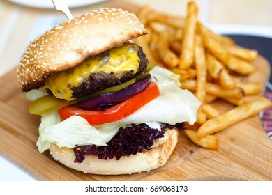 Cheese hamburger with french fries on wooden board
