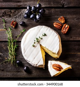 Cheese, herbs, nuts and grape on dark wooden table. Overhead view.